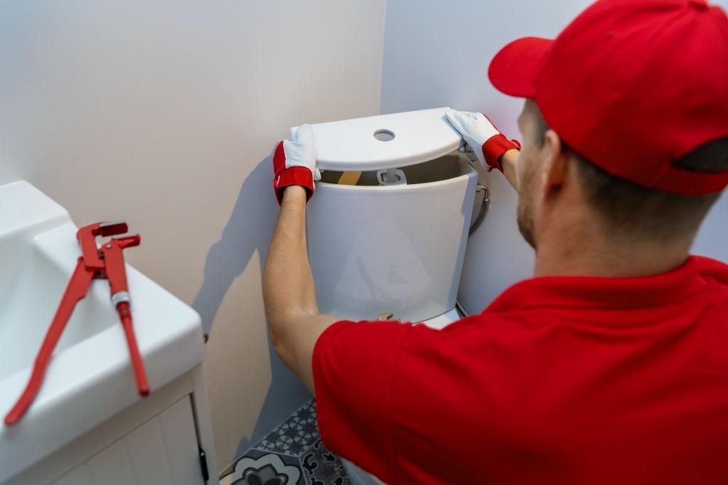 plumbing services - plumber working in bathroom installing toilet wc water tank